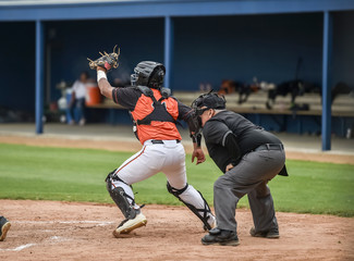 Baseball Catcher catching the ball in front of an umpire during a game