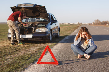 Breakdown alongside road. Male tries to repair car, call by cell phone in road assistance, can`t solve problem by himself, stressful woman sits crossed legs on asphalt near warning red sign.