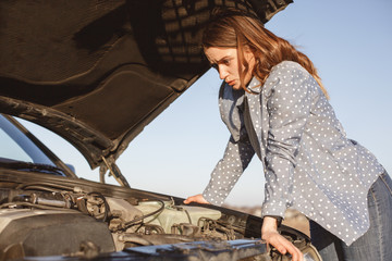 Helpless female looks desperately at opened car hood, has breakdown on road, can`t solve problem, has shocked expression, needs help or assistance, looks at demaged engine. Stopped automobile