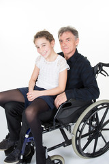young granddaughter visiting her disabled grandfather in wheelchair and enjoying each other