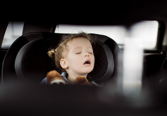 Cute girl with mouth open sleeping in car seen through vehicle seat