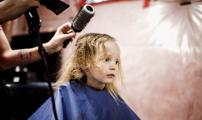 Cropped hands of hairdresser using hair dryer on girl in salon