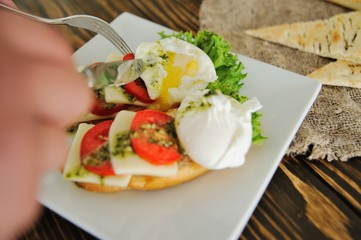 breakfast bread with egg poached, tomato, cheese and greens close-up on a wooden background