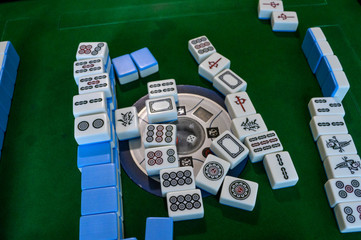 Chinese dominoes on a green table.