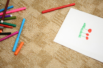 children draw with pencils sitting on the floor