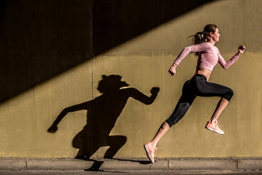 Young fit blonde woman jumping in the street