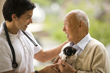 Male nurse laughs and talks with a senior man holding a puppy.