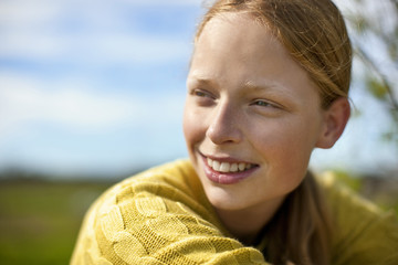 Smiling teenage girl in rural setting.