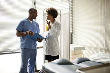 Female doctor and male nurse discussing patient files.