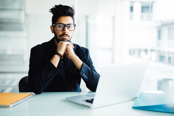 Indian business Man using laptop with hands hand on chin in his modern office