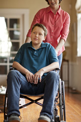 Teenage boy sitting in a wheelchair while his mother stands behind him.