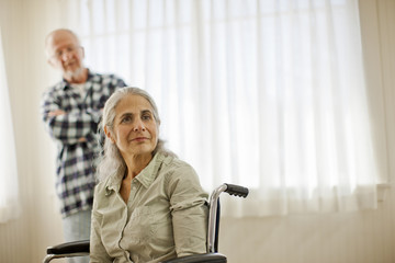 Pensive senior woman sitting in a wheel chair while her husband looks on.
