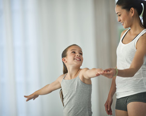 Smiling young girl stretching her arms while doing yoga.