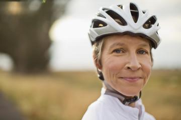 Portrait of a senior woman wearing a bike helmet.