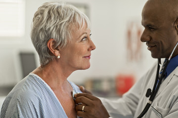 Mature woman gazes flirtatiously at the young doctor checking her heartbeat.