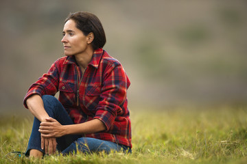 Portrait of a thoughtful mid adult woman sitting in a grassy field.