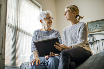 Senior woman and adult daughter share memories.