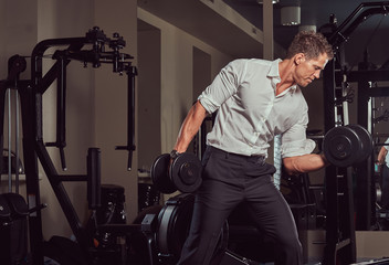 Handsome muscular businessman in formal clothes doing exercise with dumbbells in the gym.
