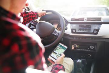 Mann schaut während der Fahrt auf sein Handy