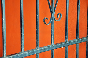Close up on a metallic fence on bright orange wall background