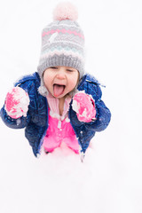 Little girl catching falling snow in mouth