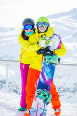 Full-length photo of sporty woman and man with snowboard against backdrop of mountains