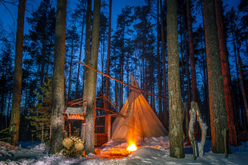 Tipe in the forest. The wigwam in the winter forest. Living in the forest. Night forest with a fire.