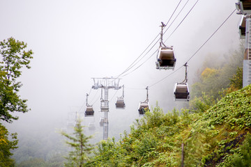 Image of funicular in mountains against background of misty sky