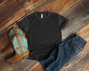 Mockup of blank gray tshirt on rustic wood background with cowboy boots and jeans