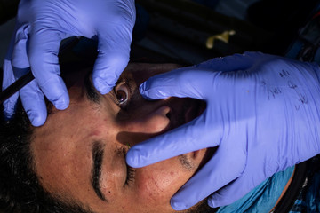 Border patrol agent checks eyes of man caught illegally crossing into the U.S. from Mexico near McAllen, Texas, U.S.