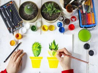 Artist paintes a cactus compositions. Artist workplace surrounded with paint, gouache, brushes and other art supplies, top view