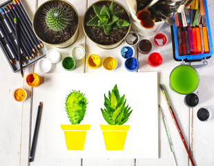 Artist workplace with picture of cactus, surrounded paint, gouache, brushes and other art supplies, top view