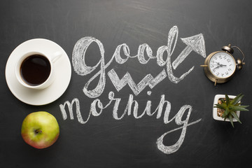 A white cup of coffee with an alarm clock and an apple and a good morning inscription. Concept of a cheerful and kind morning