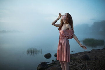 Beautiful slender red-haired model in a pink dress posing against a background of fog over the river