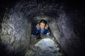 Man explores narrow passage in ancient abandoned underground chalky cave monastery