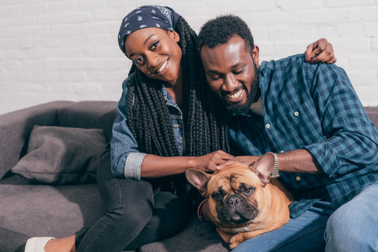 smiling young african american couple sitting on couch with french bulldog