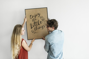 Caucasian couple hanging a frame on white wall