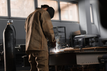 rear view of manufacture worker welding metal with sparks at factory