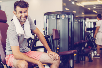 Portrait of happy young sportsman with towel around his neck sitting on weight-lifting machine in modern gym and having rest after hard training
