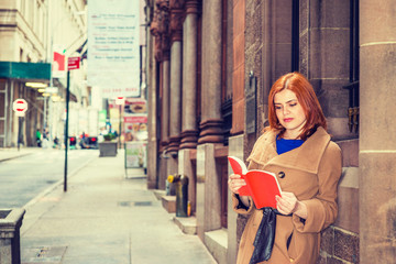 I love reading. Young American Woman reading red book outdoor in New York, wearing long brown woolen overcoat, standing against vintage wall with windows on street in winter day..