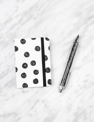 Black and white diary and pen on marble background