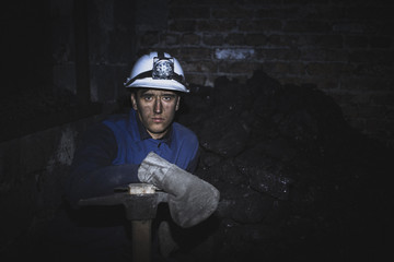 a miner with a pick sitting on the corner all tired and dirty from the coal dust after a hard work in the mine