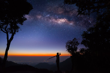 Silhouette of a Professional photographer shooting a milky way