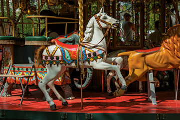 Colorful carousel with white horse in a park of Annecy. An historical and lovely lakeside town located at the department of Haute-Savoie, southeastern France.