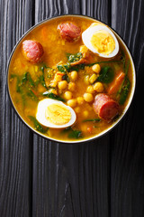 Stewed Potaje de garbanzos chickpeas, spinach, chorizo sausages, boiled eggs close-up in a bowl. Vertical top view