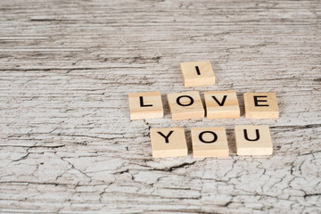 i love you letters on wooden planks, white rustic wooden table as background