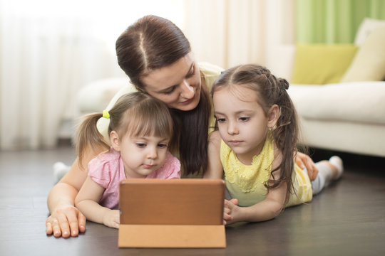 Mother with children use ipad lying on floor in living room