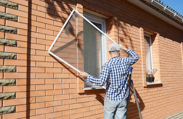 Contractor installing mosquito wire screen on house window to protect from insects.