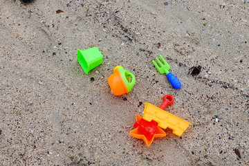 Travelers' shoes are placed at the beach. The sand toys and toys are placed at the beach.