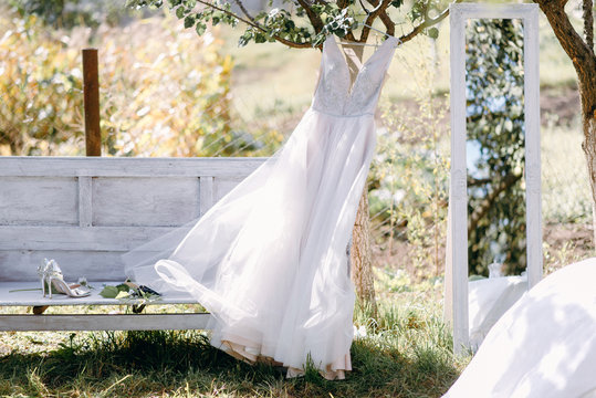 Wedding dress in the garden before the dress of the bride near the vintage bench and mirror